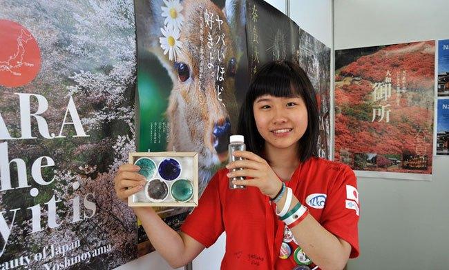 U Kyoka enseña el vidrio de colores que ha obtenido su equipo con excrementos de ciervo en Japón. / SINC
